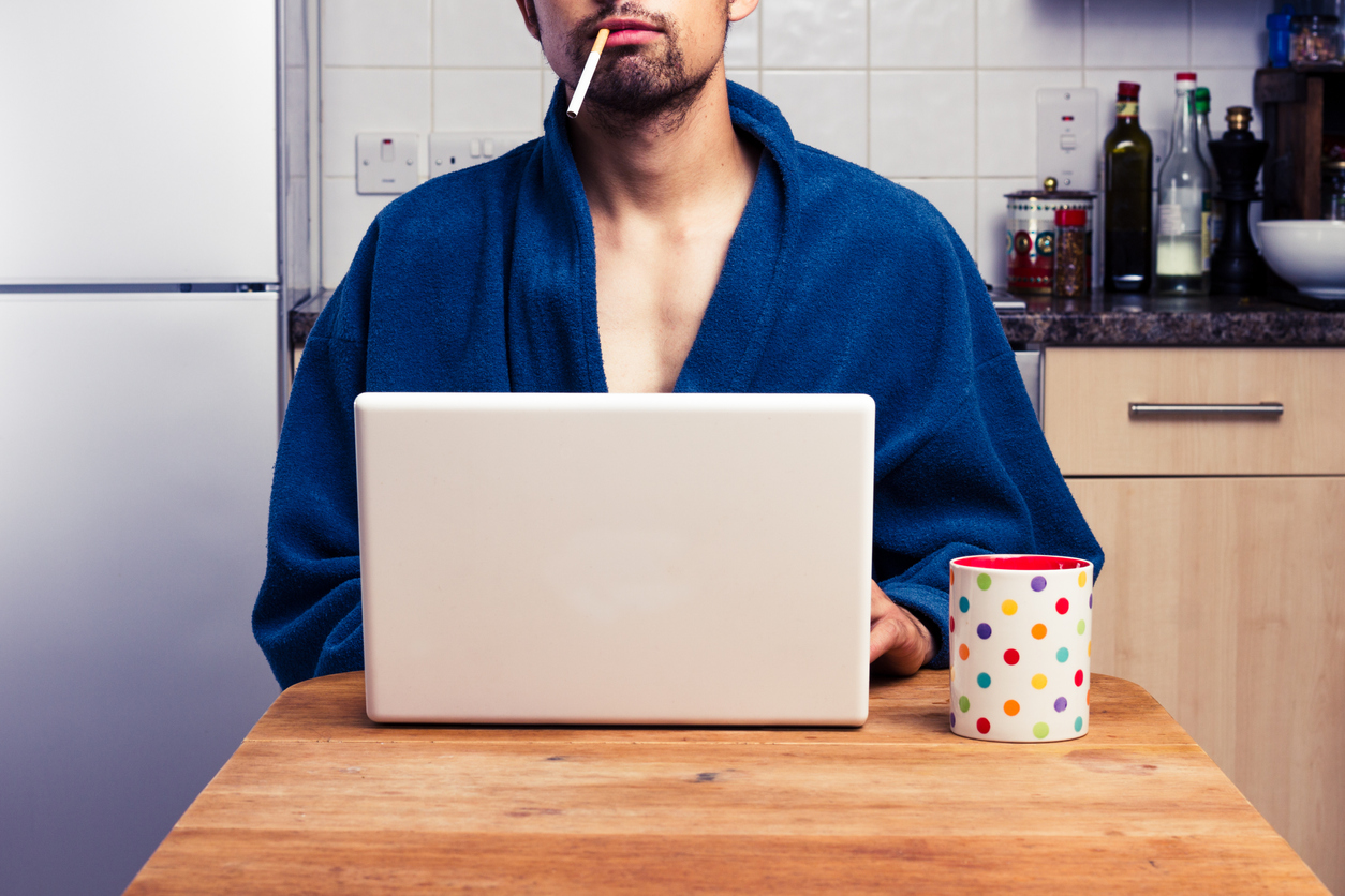 Young man is working from home. He can smoke wear a bathrobe and do whatever he wants.