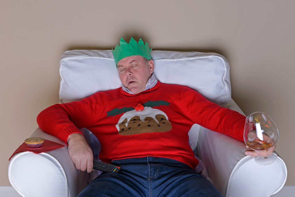 A Christmas tradition - Dad has fallen asleep in an armchair after dinner in front of the TV, he's wearing the jumper he got for Christmas and is about to drop a glass of brandy.