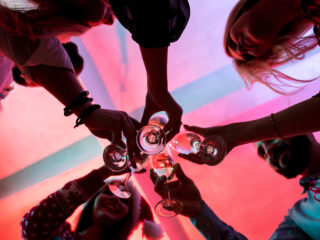Young people with glasses of champagne at Christmas party. Friends celebrate New Year at home