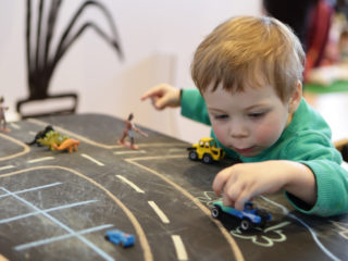 Child playing with toy car on a table