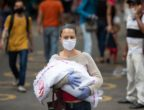 CARACAS, VENEZUELA - MAY 28:  A woman wearing a mask and latex gloves carries her baby as she walks down the boulevard of the slum Catia during the end of the second month of Quarantine on May 28, 2020 in Caracas, Venezuela. NGO Human Rights Watch questioned figures released by the Maduro Government and issued an alert about the possible collapse due to the spread of COVID-19 in Venezuela due to its health and humanitarian crisis. As of May 25, Venezuela has officially confirmed 1,121 positive cases of  COVID-19. (Photo by Leonardo Fernandez Viloria/Getty Images)