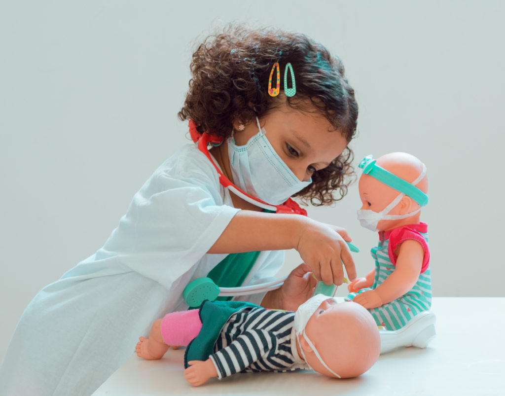 A little girl playing the doctor gives her patient an injection, they all wear protective masks