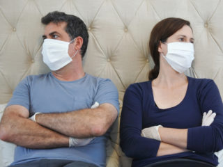 Upset couple in self isolation wearing face mask and protective gloves bored in home bedroom sitting on bed looking away.
