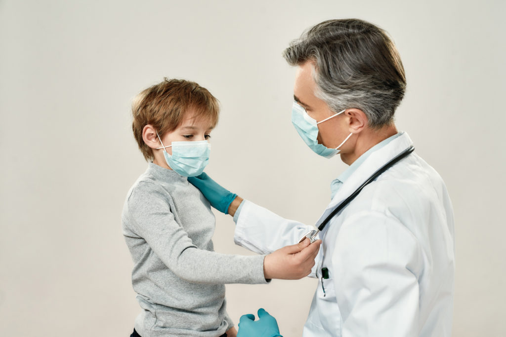 Professional mature doctor and little patient in protective masks. Male pediatrician working with little boy while standing against grey background. Healthcare, medicine. Children at clinic, hospital
