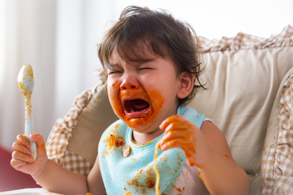 Adorable little toddler girl or infant baby crying when unsatisfied when finished eating food on baby chair. Cute infant girl get hungry and want more food. Mix race daughter get dirty Kid get tantrum