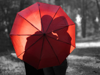 silhouette of lovers kissing under a red umbrella on a blurred background