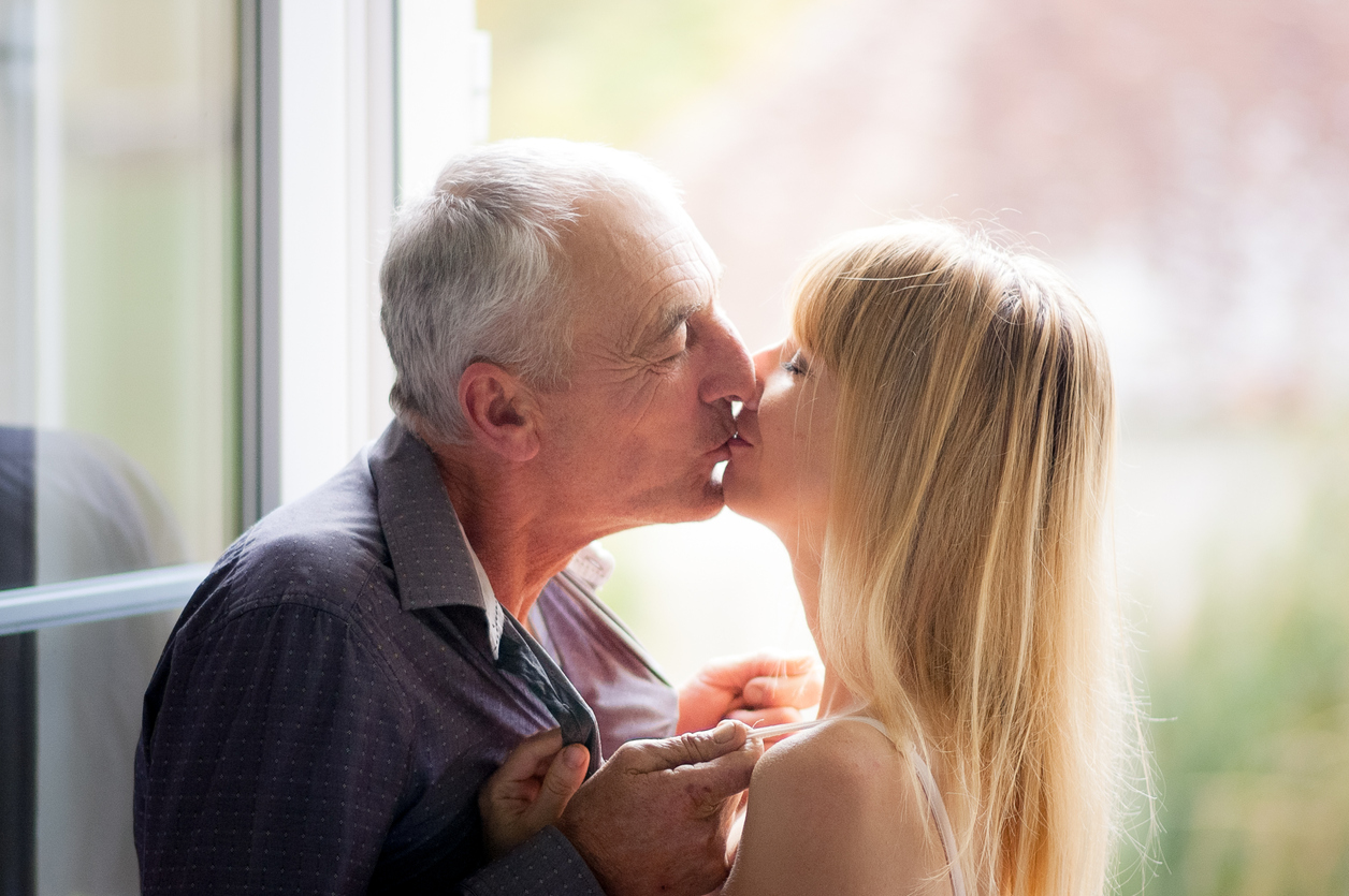 Lovely Couple with Age Difference Kissing near Opened Window inside the House During Summer Time