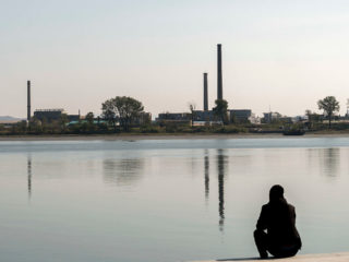 DANDONG, LIAONING PROVINCE, CHINA - 2016/10/12: A man rests beside the Yalu River, overlooking the skyline of Sinuiji of North Korea, where there are a mill factory with high chimneys.  Dandong is the largest Chinese frontier city, bordering with Shinuiju of North Korea across the Yalu River. (Photo by Zhang Peng/LightRocket via Getty Images)
