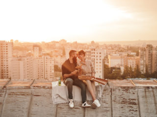 Cheerful young man and woman smiling and enjoying pizza while sitting ob barrier during romantic date in evening on rooftop