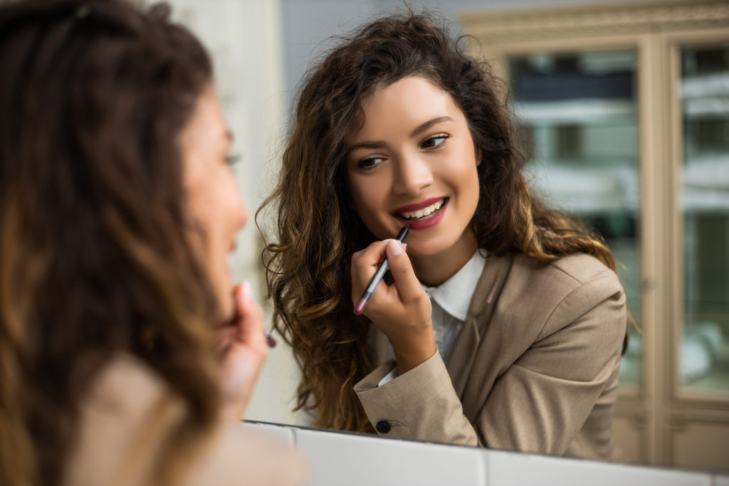 Businesswoman is applying  lipstick while preparing for work.