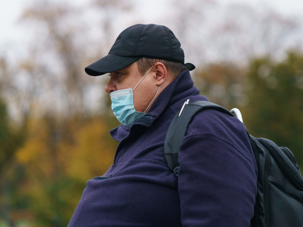 Moscow, Russia - October 12, 2020: Man wearing cap at the city street. Coronavirus pandemic time. He wear / put on / use protective face masks outdoors too. Autumn day.