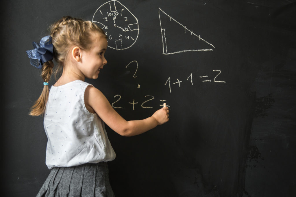 Cute girl schoolgirl near blackboard with chalk in hand,the concept of education and school life