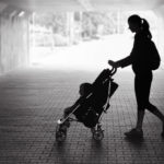 Single mother walking in city tunnel with baby in stroller.