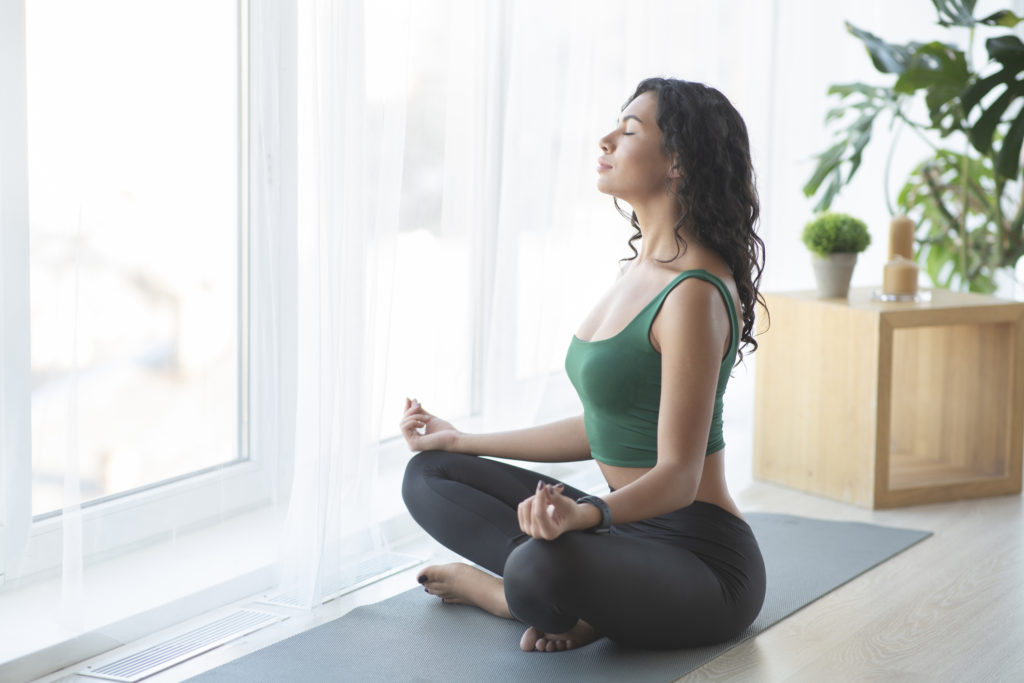Clear your thoughts. Young sporty woman practising yoga in lotus position, home atmosphere, copy space