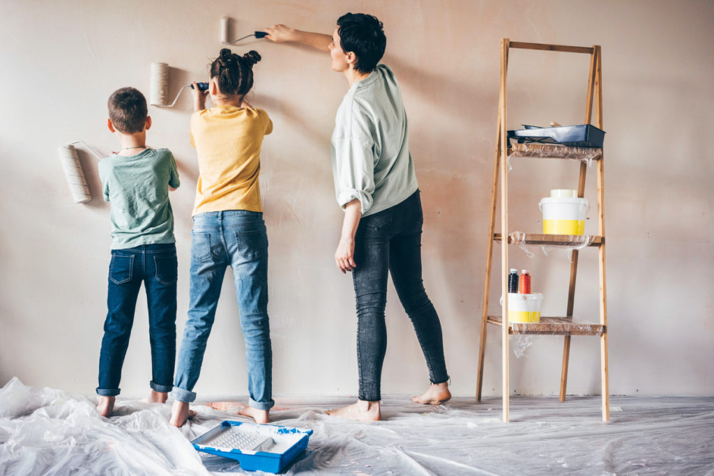 Happy mother, daughter and son painting wall with roller. Mom teach her children painting with roller at home.