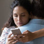 Close up of bored young Caucasian woman hug man texting messaging with lover on smartphone online. Unhappy wife embrace husband cheating on web on cellphone. Family, relationship problem concept.