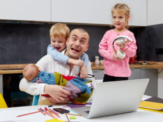Father with a newborn baby in arms working from home during quarantine and closed school. coronavirus outbreak. Young businessman freelancer works on laptop with children playing around.