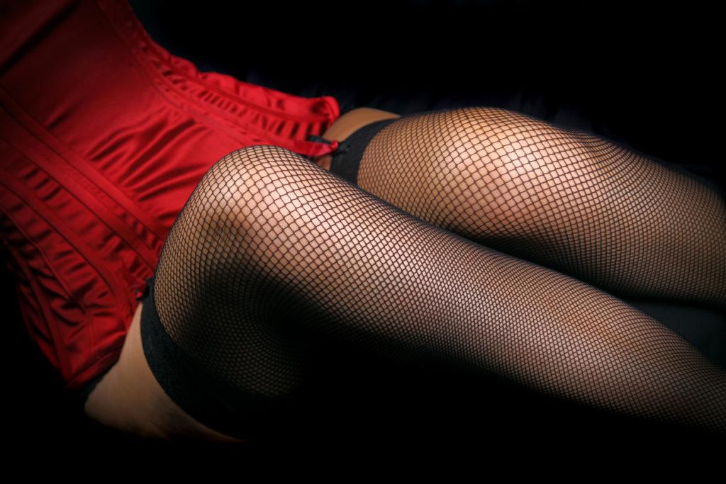 Woman's legs in sexy black fishnet stockings. Studio shot.