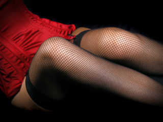 Woman's legs in sexy black fishnet stockings. Studio shot.