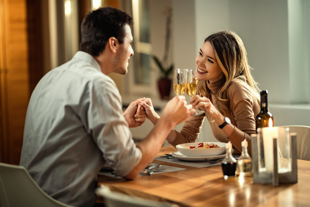 Happy woman and her boyfriend holding hands while toasting with Champagne while having dinner at dining table.