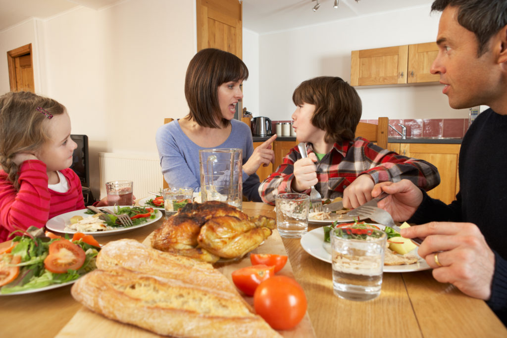 Family Having Argument Whilst Eating Lunch Together In Kitchen Sitting At Table Yelling