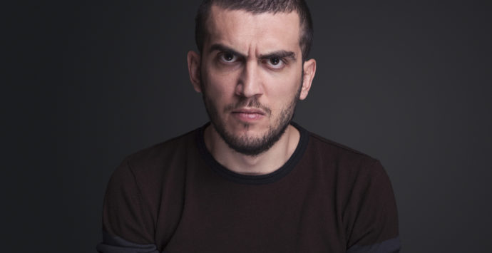 Angry young adult  over gray background ,studio shot