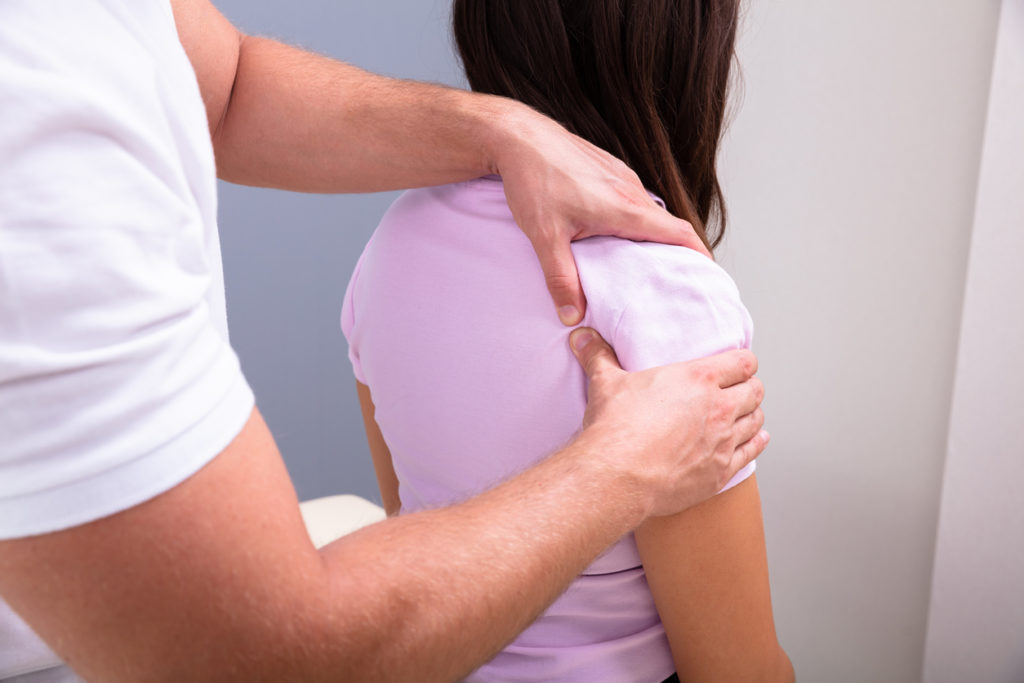 Professional Male Physical Therapist Massaging The Injured Shoulder Of A Woman Slowly In Medical Clinic