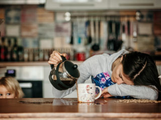 Tired mother, trying to pour coffee in the morning. Woman lying on kitchen table after sleepless night, trying to drink coffee