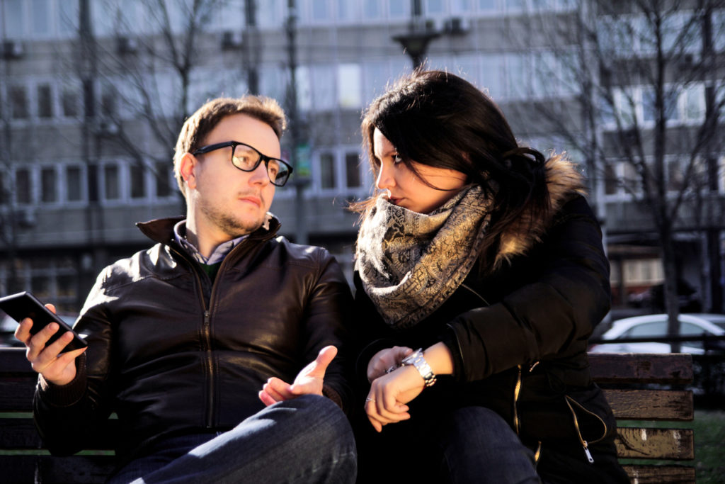 Couple on a park bench looking at each other, guy holding smartphone and the girl shows on her watch.
