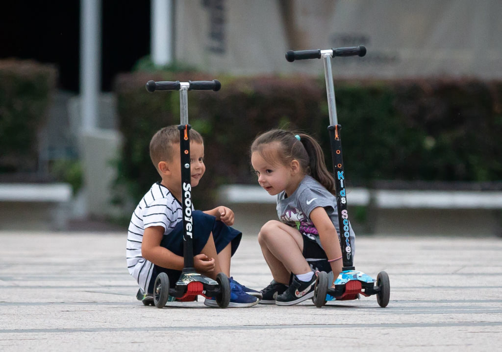 A boy and girl plays with their scooter in the city during the new Coronavirus disease (COVID-19) after the decrease of coronavirus infected in Belgrade, Serbia on August 5, 2020. The number of coronavirus infections is decreasing throughout Serbia. The government mandates the mandatory use of masks indoors and outdoors to halt the spread of the coronavirus disease (COVID-19).  (Photo by Nikola Krstic/NurPhoto via Getty Images)