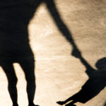 Shadows silhouettes of mother and son pulling her hand on summer promenade in sepia black and white