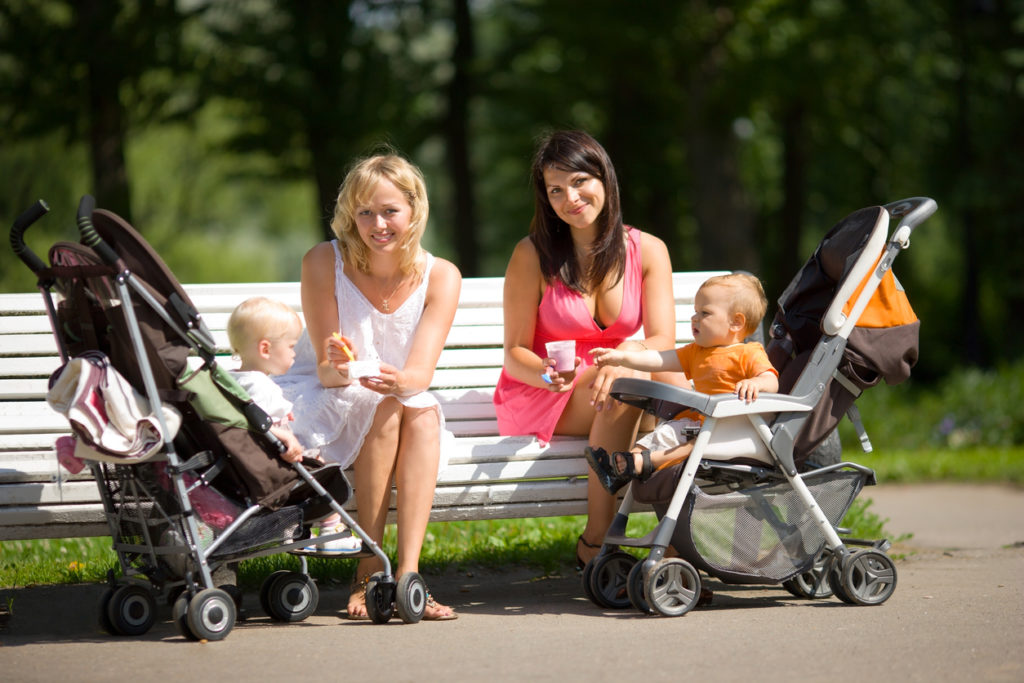 Two mothers spoon feeding their babies sitting on bench