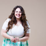 Laughing happy plus size model in casual clothes, fat woman on beige background, body positive concept