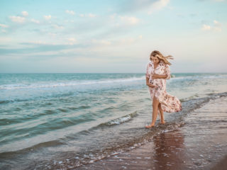 Beautiful happy young pregnant woman in a summer light dress hugging her belly and walks along the sea waves on a sunny summer evening during vacation. Natural Parenthood Concept. Copyspace