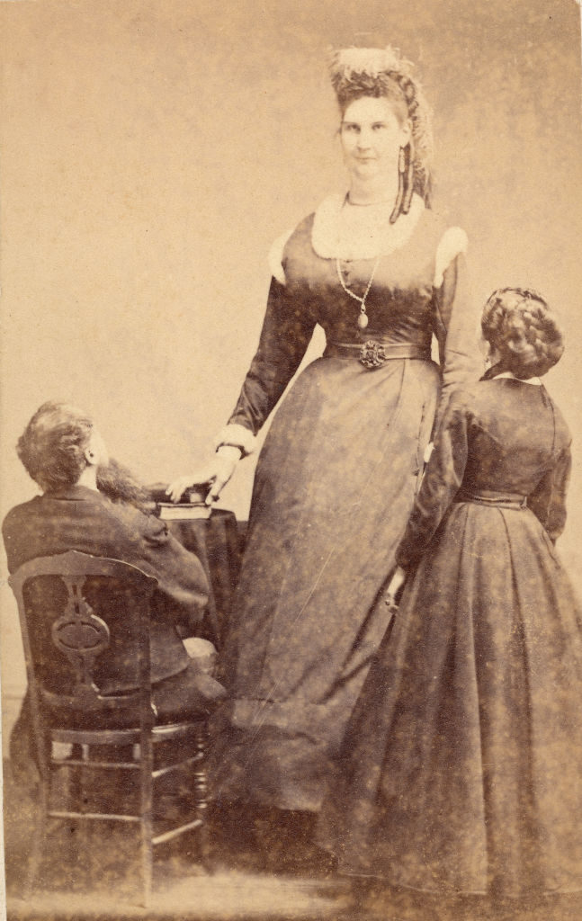 Canadian circus performer Anna Haining Swan Bates (1846 - 1888) poses next to her father Alexander Swan (seated) and her mother Ann Haining Swan, a woman of average height, 1870s. Anna, who stood over 7 1/2 feet tall, was discovered by PT Barnum in 1862 and joined the circus. In 1870, she met another one of Barnum's performers, Captain Martin Van Buren Bates, himself almost 8 feet tall. They married in 1871. (Photo by Blank Archives/Getty Images)